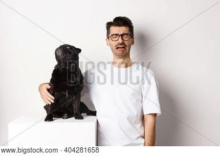 Image Of Sad Crying Man Hugging His Cute Black Pug, Dog Looking Curious At Upper Left Corner Promo L