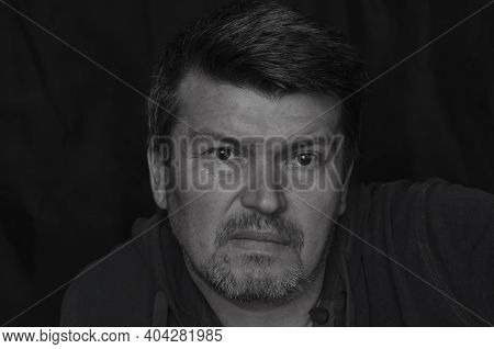 Monochrome Portrait Of A Middle-aged Man Looking Past The Camera. Caucasian Man With Gray Stubble.