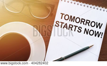 Tomorrow Starts Now - Text On Paper With Cup Of Coffee And Glasses On Wooden Background In Sinlight.