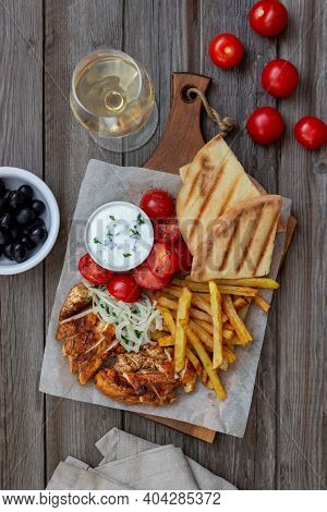 Greek Dish Gyros With Chicken, French Fries, Tomatoes, Onions And Pita. Greek Cuisine.