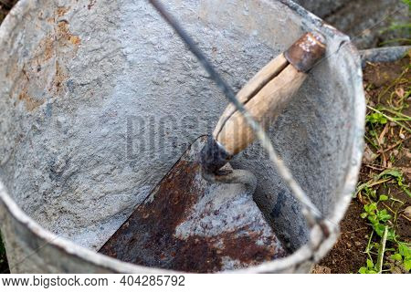 The Use Of Cement For Construction. Knead The Cement In A Bucket. The Remains Of Cement After Work