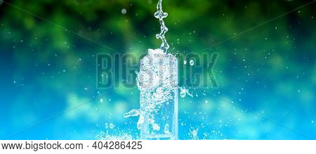 Drink Water Pouring In To Glass Over Sunlight And Natural Green Background.water Splash  In Glass Se