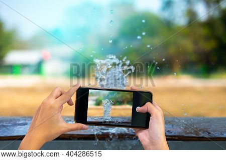 Two Hand Holding Mobile Phone And Take A Photo Drink Water Pouring In To Glass Over Sunlight And Nat