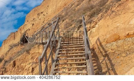 Wooden Staircase On A Yellow-brown Clay Slope. Close-up. A Small Piece Of Blue Sky With White Clouds