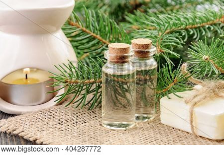 Two Bottles Of Spruce Essential Oil, Natural Soap And Fir Branches Behind On Linen Napkin.