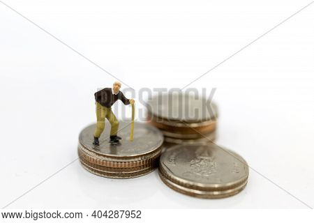Miniature People: Oldman Standing On Coins Stack, Retirement Planning Concept.
