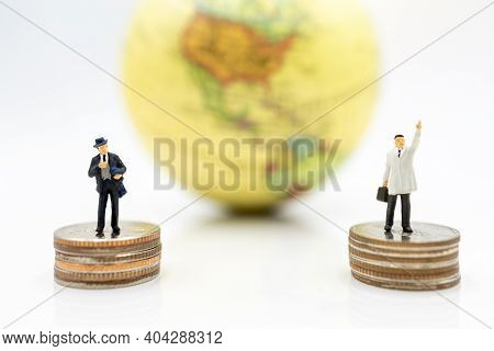 Miniature People: Businessman Standing On Coins Stack With Globe. Finance And Business Concept.
