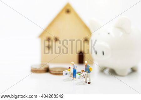 Miniature People: Parent And Children Standing With Home And Piggy Bank , Home Purchase Planning And