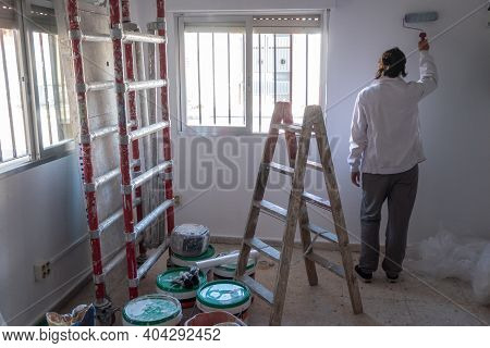 Young Woman Painting Interior Wall With White Paint.  Paint Cans And Painter Ladder.