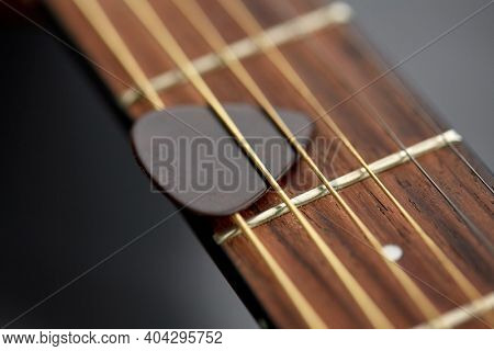 leisure, music and musical instruments concept - close up of bass guitar neck with pick between strings