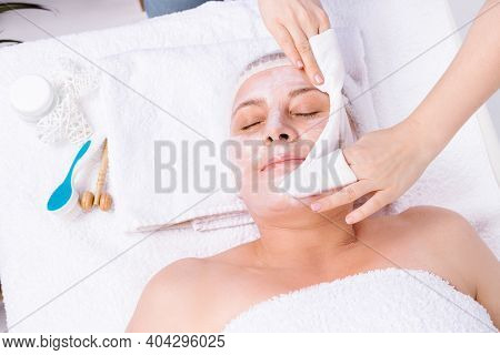 The Beautician Wipes The Mask From The Senior Womans Face, Close-up Portrait. Beautician Makes A Fac
