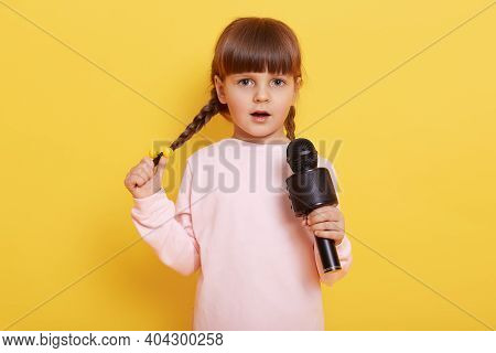 Shy Small Female Kid With Pigtails Singing In Microphone, Cute Little European Girl Wearing Pale Pin