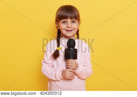 Cute Little Girl With Microphone Posing Isolated On Yellow Color Background, Singing Or Telling Poem
