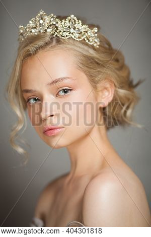 Beautiful Blond Woman In The Image Of A Bride With A Tiara In Her Hair. Picture Taken In The Studio