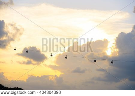 Silhouette Of Singapore Cable Car Transportation To Sentosa Island On The Evening
