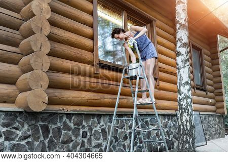 Young Adult Beautiful Slim Sporty Caucasian Woman In Overalls Stand On Metal Ladder And Washing Wind