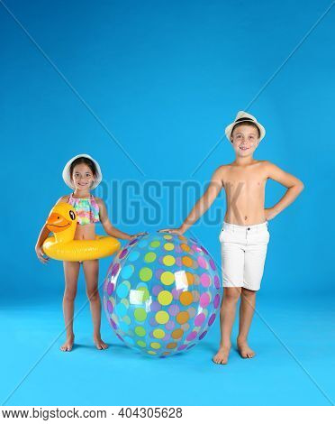 Cute Little Children In Beachwear With Inflatable Toys On Light Blue Background