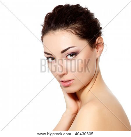 young beautiful woman with clean skin touching her face with hand over white background