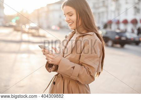 Young Beautiful Business Woman With Long Hair And A Beautiful Smile In The Spring City In A Fashiona
