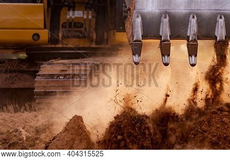 Selective Focus On Metal Bucket Teeth Of Backhoe Digging Soil. Backhoe Working By Digging Soil At Co