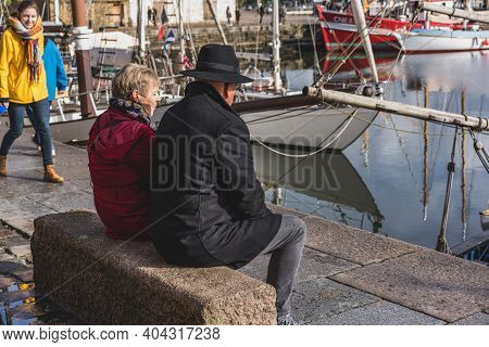 Honfleur, Calvados / France - 3 November 2019: Senior Couple Sitting Near The Harbor Of Honfleur.