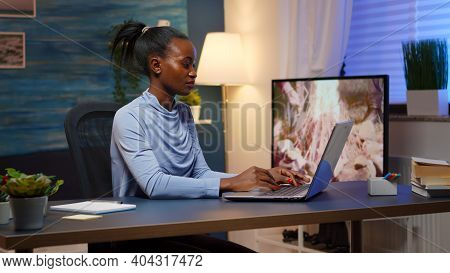 Overworked Black Entrepreneur Working From Home Late At Night On Laptop. Tired Focused Employee Usin