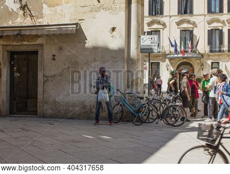 Lecce, Italy April 23, 2018 Cycling Tourism, A Group Of Tourists Talking On The Street With A Guide.