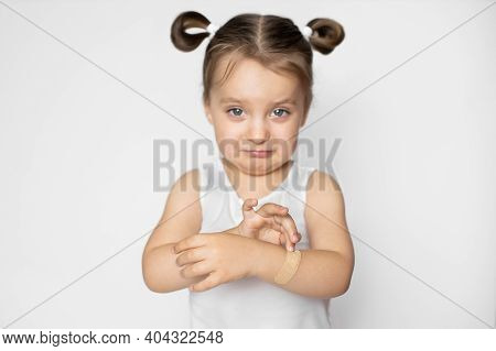 Portrait Of Cute Pretty Crying Child Girl, Feeling Pain Because Of Wound On Her Arm, Applying Adhesi