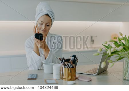 Photo Of Good Looking Woman Applying Face Cream On Face Looks At Herself In Mirror Cares About Compl