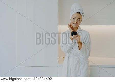 Attractive Female Applies Moisturising Cream On Face Takes Care Of Her Complexion And Skin Holds Mir