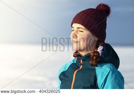 Beautiful Young Relaxed Woman Enjoying Cold Sunny Winter Weather, Smiling, Relaxing Outdoors With He