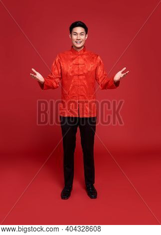 Happy Chinese New Year. Handsome Asian Man With Open Hand Gesture Of Introduce Isolated On Red Backg