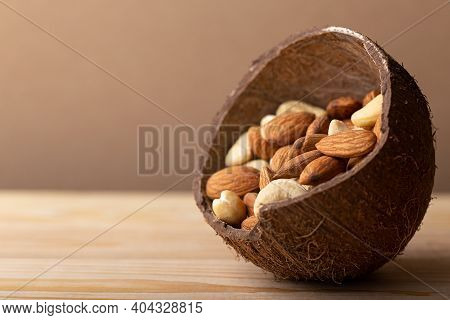 Mix Of Almonds, Cashew Nuts In Coconut Bowl On Brown Background Close Up. Vegan Protein Source