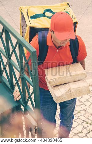 Confident Courier Delivering Order And Entering To Client Yard. Deliveryman Wearing Jeans, Red Cap A