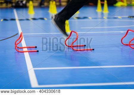 Athlete Jumping Over Red Training Hurdles On Indoor Practice Session. Futsal Training Equipment In T