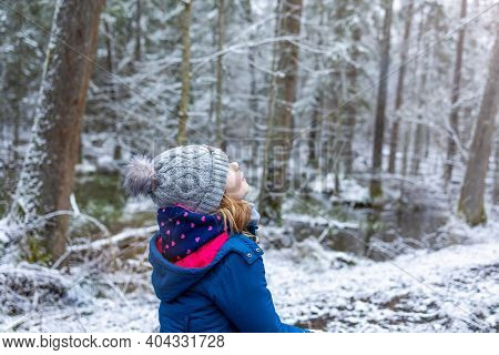 Little girl enjoying a walk through the woodland in winter, Bialowieza Forest, Poland