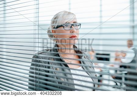 Close Up. Serious Business Woman Looking Through Office Window