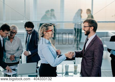 Happy Colleagues Shaking Hands With Each Other Near The Desktop.