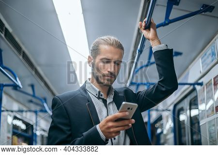 Business Man Checking His Email Correspondence In The Subway.
