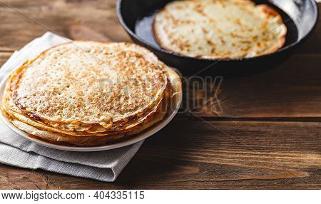 Traditional Russian Crepes Blini Stacked In A Plate And Pancake In A Cast-iron Frying Pan On Dark Wo