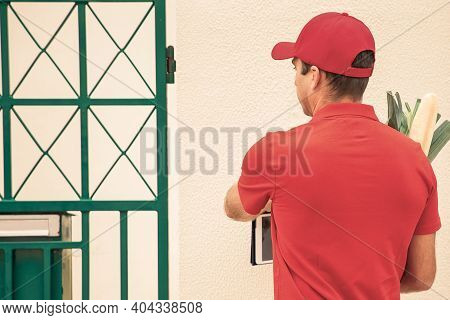 Back View Of Deliveryman Ringing Doorbell And Holding Tablet. Professional Courier Delivering Vegeta