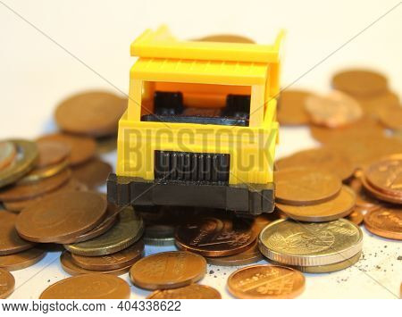 Yellow Toy Dump Truck On The Coins