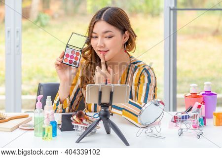 Beautiful Young Asian Woman, Vlogger,  Reviewing Beauty Products On A Video Blog Through Her Phone A