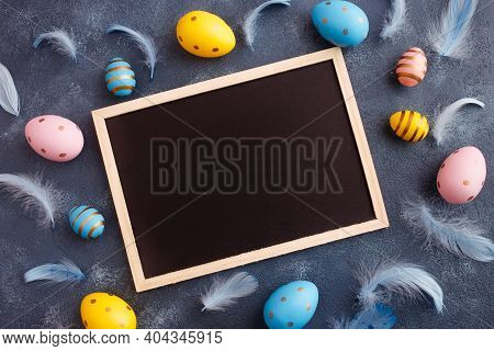 Easter Greeting Card Concept. Easter Colored Eggs With Feathers With Blackboard On Blue Art Backgrou