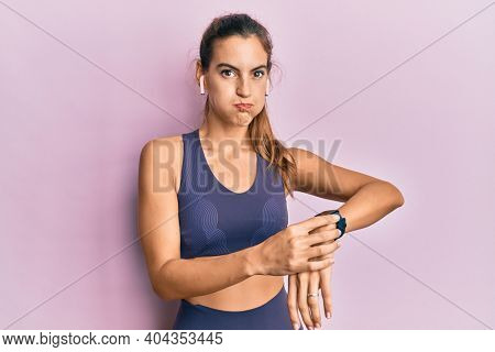 Young beautiful woman wearing gym clothes, using earphones and smart watch puffing cheeks with funny face. mouth inflated with air, catching air.