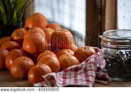 Tangerines (oranges, Clementines, Citrus) On Wooden Table With Glass Jar And Checkered Napkin, Windo