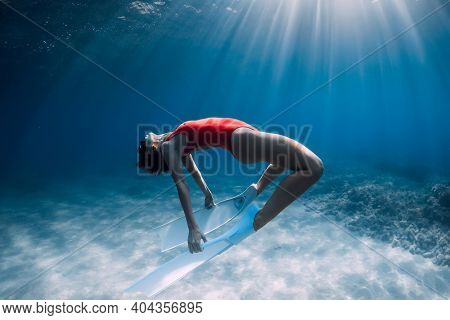 Woman Freediver In Red Swimsuit With White Fins Posing Underwater Over Sand In Tropical Ocean. Sport