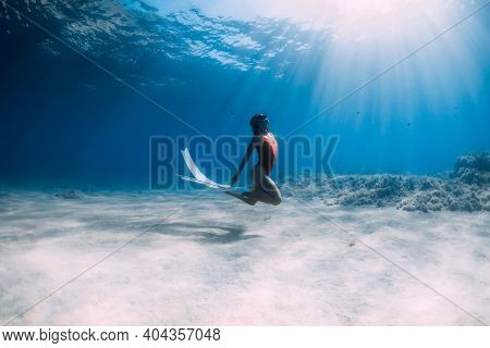 Woman Freediver In Red Swimsuit With White Fins Glides Underwater Over Sand In Tropical Ocean. Sport