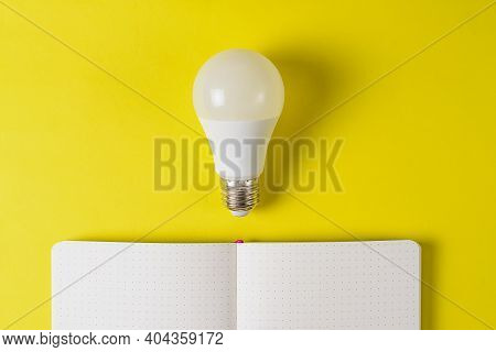 Opened Close Up White Notebook With A Light Bulb On A Bright Yellow Background. Inspiration Search C