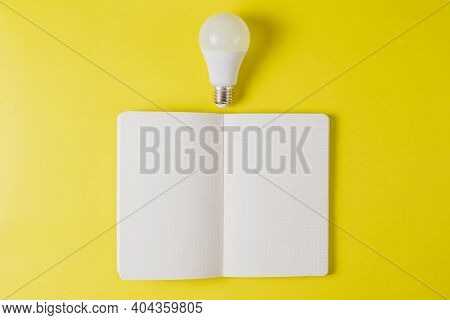 An Open White Notebook With A White Light Bulb On A Bright Yellow Background. Inspiration Search Con